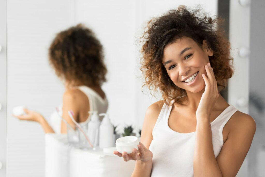 Afro Girl Using Face Cream Standing In Bathroom